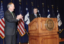 Evans applauding Gutierrez on stage with U.S. and Commerce flags in background. Click for larger image.